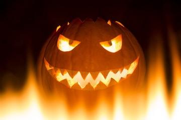 Gruseliger geschnitzter Halloween Kürbis im Feuer welches brennt. Der große Helloween Kürbis hat ein Gesicht dass frech ist und lacht mit leuchtenden Augen und einem Mund mit Zähnen. Perspektive unten