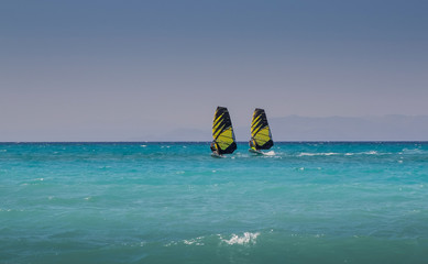 Zwei Windsurfer im Meer fahren parallel, mit ähnlichem Segel.