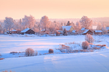 The village at sunset in a snow field.