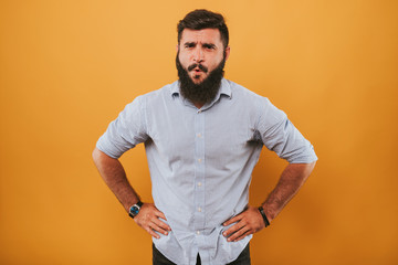 portrait of handsome smiling man isolated on yellow studio background posing to the camera and making funny faces