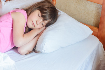 young child girl sleeping in bed at home, indoor portrait