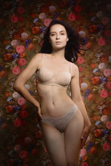 Beautiful sensuality girl on a flower wall background