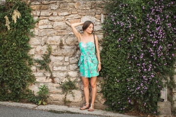 cute girl standing at the wall flower