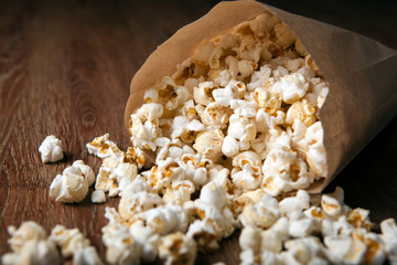 salted popcorn in a paper bag on a wooden table