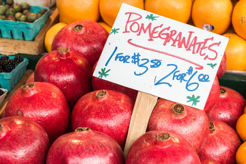 Pomegranates on Display with Handmade Sign with Name and Product in Farmers Market