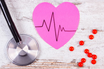 Heart of paper with cardiogram line, stethoscope and supplement pills, medicine and healthcare concept
