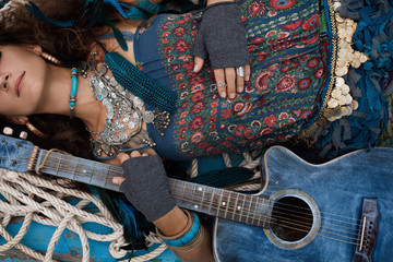 Atrractive young hippie woman with guitar outdoors