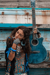 Boho woman with guitar at old boat background