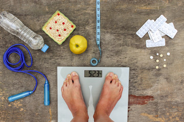 Concept of different ways to lose weight. Scales, tape measure, apple, oatmeal, jump rope, water, medicine.