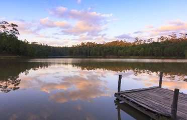Beautiful natural view of serene lake in sunset with a wooden dock beside the lake.