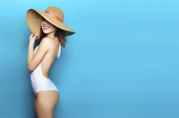 sexy girl in panama in white bikini on a blue background stands sideways and hat covering his face