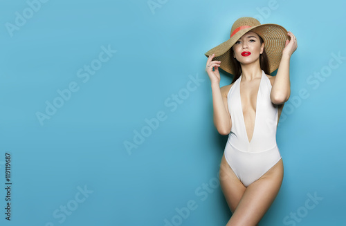 dbd18b94f1 sexy girl in panama in white bikini on a blue background stands sideways  and hat covering his face