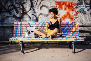 Young woman sitting on colourful painted bench looking at cell phone
