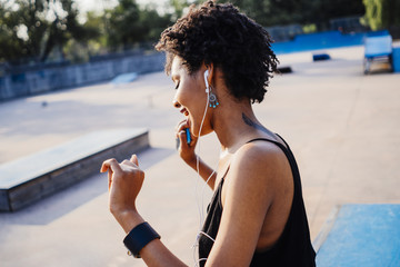 Smiling young woman with earphones dancing in a skatepark