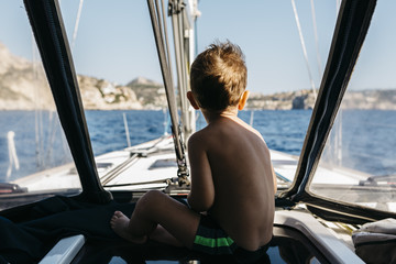Back view of little boy sitting on a sailing boat