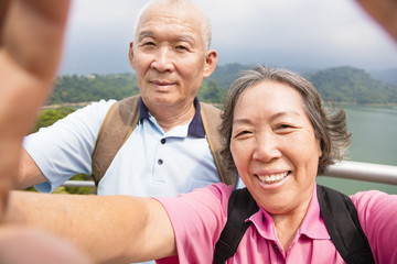 happy senior couple taking picture with smart phone selfie