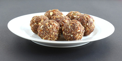 Indian sweet food dry fruits and nuts laddu, which is a traditional, healthy, nutritious and popular dish, is made from items like dates, raisins, almonds, cashew nuts and flaxseeds, in a plate.