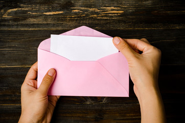 Pink envelope and blank white card are hold by hand on wooden background