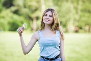 Young girl holding cardboard bin icon