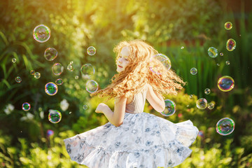 Sweet girl dancing and playing with soap bubbles enjoying a sunn