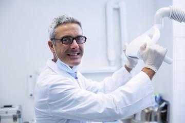 Portrait of a dentist adjusting light