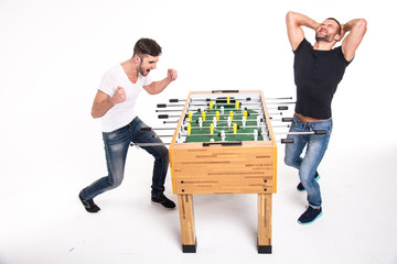 Boys play table football. The emotions of winning and losing. Wh