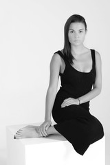 Black and white photo shooting, women sitting on cube in black dress