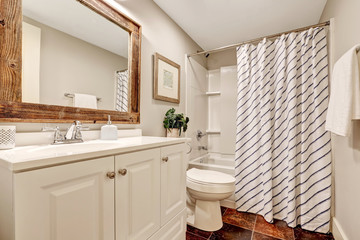 White Bathroom with vanity cabinet and wooden framed mirror.