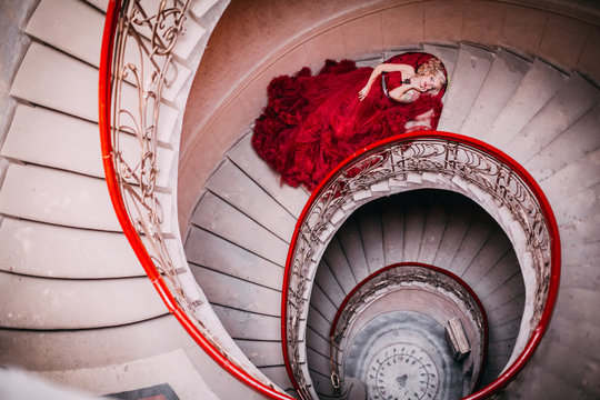 Beauty and shape. Young beautiful woman standing on old round staircase. Blonde girl with tatoo in red cloud dress embracing. Advertising picture