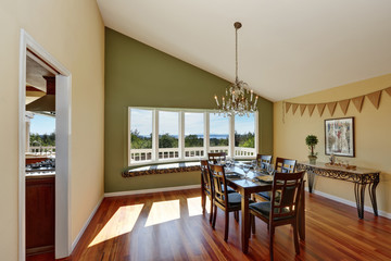 Elegant dining room with contrast olive wall and hardwood floor