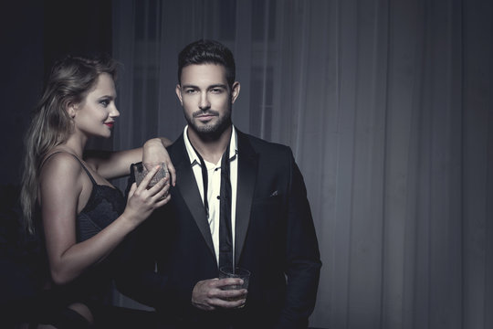 Rich macho young man drink whiskey with lover