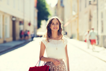 happy woman with shopping bags walking in city