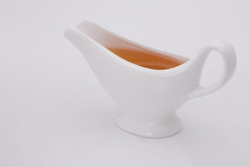sauce in white gravy boat on a white background