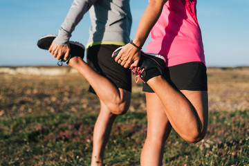 Sporty couple stretching legs outdoors before trail running workout outdoors. Fitness healthy lifestyle concept.