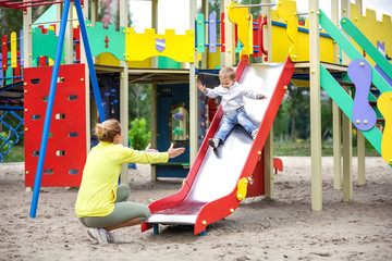 Mother catching son on playground slide