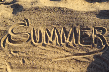 "Word ""Summer"" handwritten on the sand, top view."