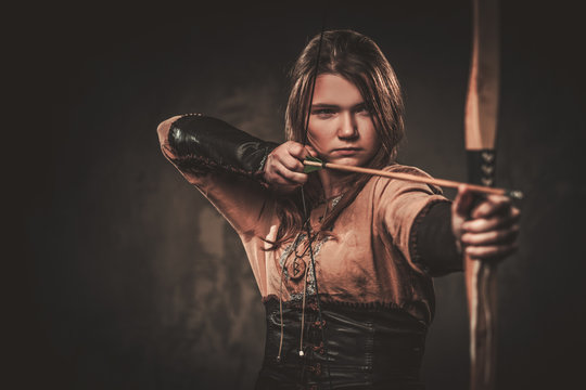 Serious viking woman with bow and arrow in a traditional warrior clothes, posing on a dark background.