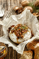 Baked Camembert with walnuts, honey  and rosemary on wooden rustic table