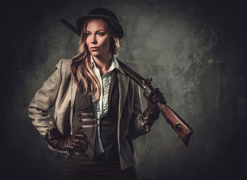 Lady with shotgun and hat from wild west on dark background.