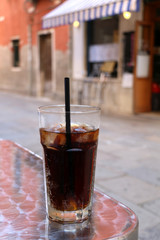 Tall glass of soda in an Italian cafe outdoor. Selective focus.