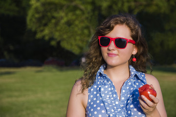 Young female with red sunglasses and blue polka dot holding a whole tomato in park