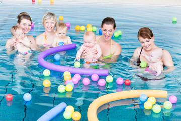 Mütter spielen mit Ihren Neugeborenen beim Säuglingsschwimmen mit Bällen und Poolnudeln