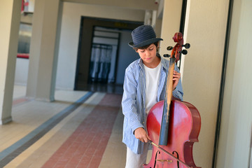 Boy fine tuning large red cello