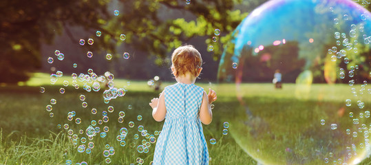Cute little girl playing the soap bubbles