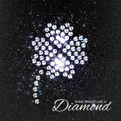 Four Leaf Clover Brilliant stones on black Denim Texture. Silver applique. Beautiful jewelry brooch with rhinestones. Ornament crystal precious, beadwork, embroidery. Fashion decor print.