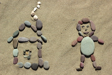 Man and house from pebble on sand background