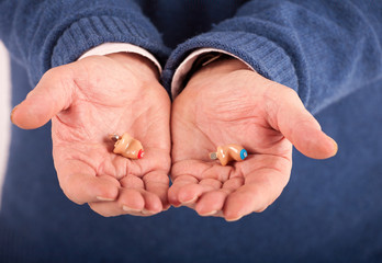 Senior man's hand showing a CIC (completely in canal)  hearing aids left and right