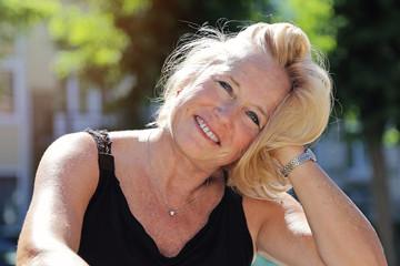 portrait jolie femme blonde senior souriante au soleil