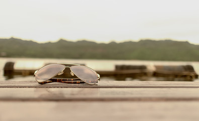 glasses Placed on a wooden floor and Mountain river sky sun