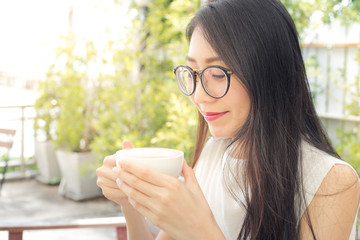 Close up of a woman taking in smell of coffee at morning in the garden.